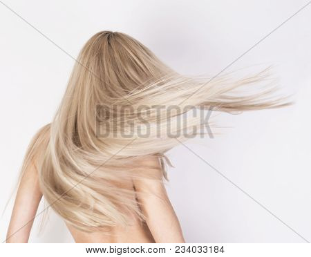 Healthy long platinum blonde hair in motion. Anonymous look from the back. poster