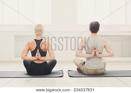 Couple In Yoga Class Making Asana Exercises. Man And Woman Do Back And Shoulders Stretching, Back Vi