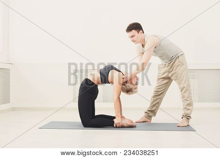Yoga Teacher And Beginner In Class, Making Asana Exercises. Slim Woman Do Back And Shoulders Stretch