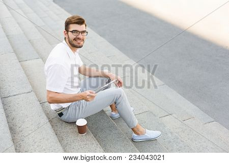 Young Happy Businessman Is Holding Digital Tablet And Drinking Coffee While Sitting On Stone Stairs,