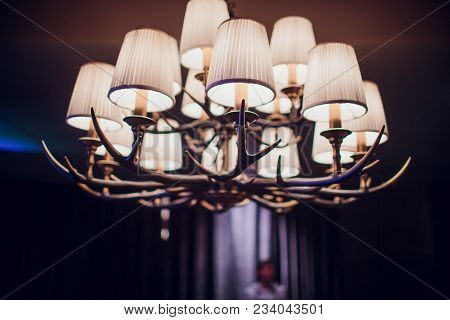 Chandelier Made Of Deer Antlers On A Blur Background