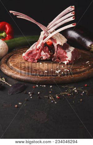 Raw Cut Rack Of Lamb. Fresh Meat On Wooden Board At Black Background. Organic Ingredients For Restau