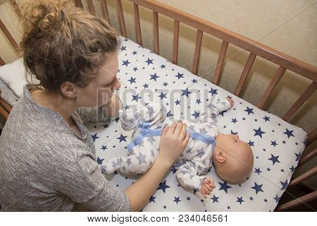 Mom Massages The Tummy Of Her Newborn Baby, Who Lies In A Crib