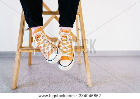 Legs Of A Girl In Orange Sneakers And Pink Socks. The Teenager In Sneakers And Dark Jeans Sits On A