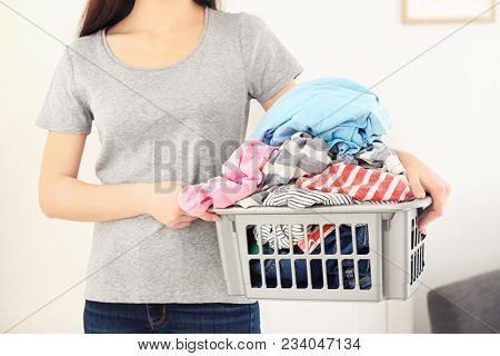 Woman holding plastic basket with clothes indoors. Laundry day