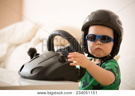 Cute Little Kid Boy In A Helmet Playing With Computer Steering Wheel. Future Driver. Getting Ready F