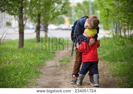 Two Little Brothers Hugging Each Other When Meeting In The Park. Cute Kid Boy Meets His Little Toddl