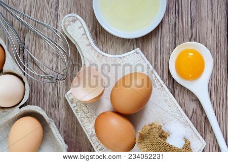 Fresh Farm Eggs On A Wooden Rustic Background. Separated Egg White And Yolks, Broken Egg Shells. Whi