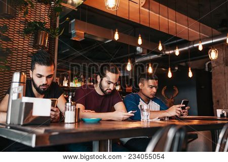 Social Media Addiction Concept. Mixed Race Friends Looking At Their Phones In Lounge Bar. Loneliness