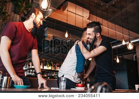 Multiracial Young Men Meeting Their Friend In Lounge Cafe. Real Emotions Of Best Friends Happy To Se