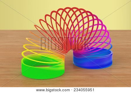 Rainbow Colored Plastic, Slinky Toy On The Wooden Table. 3d Rendering