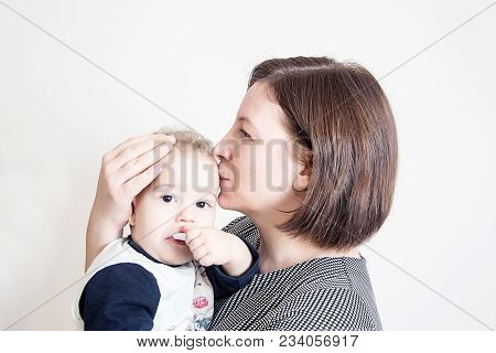 Portrait Of A Mother Who Hold On Your Arms One Year Old Son Kissing Him With Love