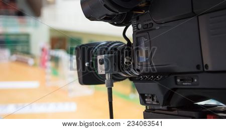 Camera lens ready to relay handball match. Blurred court background. Closeup of camera.