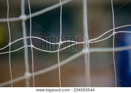 Athletic concept. Soccer nets with knots white color, close up, behind view. Blurred background