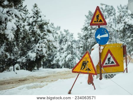 Under construction signs in snow. Warning symbols about street reconstruction. Snowy road and forest background.
