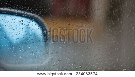Car mirror behind a transparent window with raindrops. Abstract, blurred background, space for text