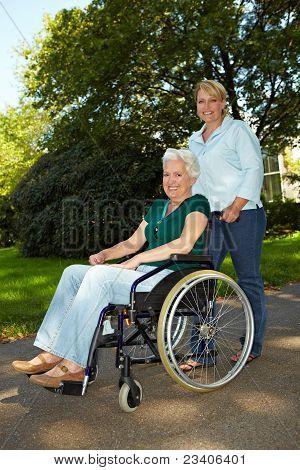 Nurse Driving Senior Woman In Wheelchair