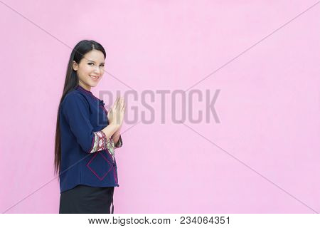 Portrait Of Asian Girl Young In Traditional Thai Dress Praying Isolated On Pink Background. Wai Sawa