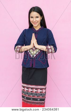 Portrait Of Young Asian Young Girl In Traditional Thai Dress Praying Isolated On Pink Background. Wa