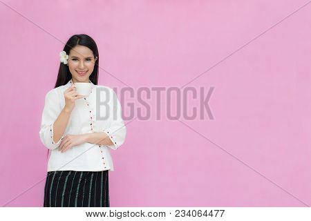 Portrait Beautiful Asian Girl In Traditional Thai Dress And Holding Coffee Cup Isolated On Pink Back