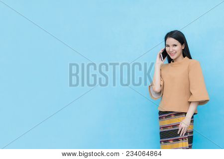 Portrait Of Asian Young Girl In Traditional Thai Dress And Holding Smartphone  Isolated On Blue Sky