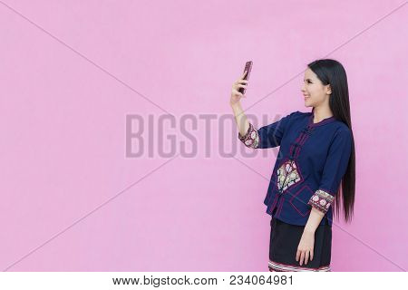Portrait Of Asian Young Girl In Traditional Thai Dress And Holding Smartphone  Isolated On Pink Back