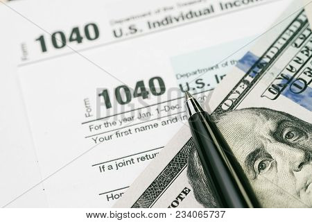 Tax Time Concept, Pen On Us Dollar Bills With 1040 Us Individual Income Tax Filling Form, Calculate
