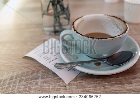 Dirty Cup Of Coffee After Drink With Receipt Slip On Wooden Table