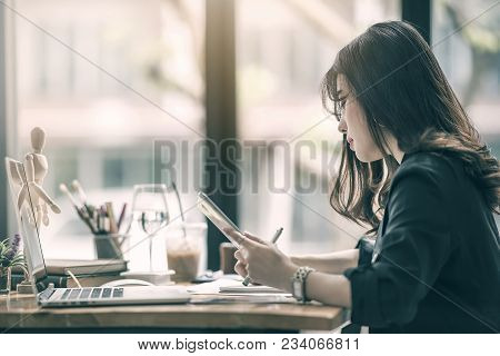Beautiful Female Designer Working With Paperwork  And Looking At Tablet Screen While Working At Mode