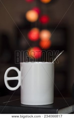 Close Up White Coffee Cup On The Book And Colorful Blur Light Bokeh In Dark Background