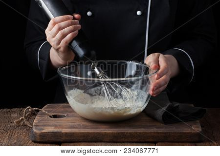 Female Chef Stirring His Batter With A Whisk On A Black Background.