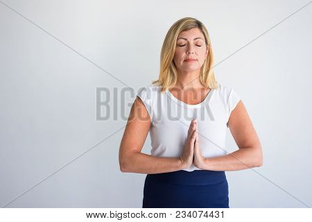 Happy Middle Aged Caucasian Woman With Closed Eyes Putting Hands Together In Meditation. Office Empl