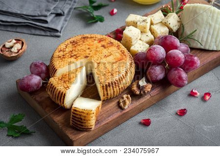 Cheese Platter With Assorted Cheeses, Grapes, Nuts Over Black Background, Copy Space. Italian Cheese