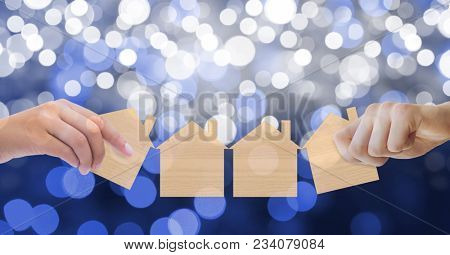 Digital composite of Cropped image of hands holding house paper cut outs against bokeh