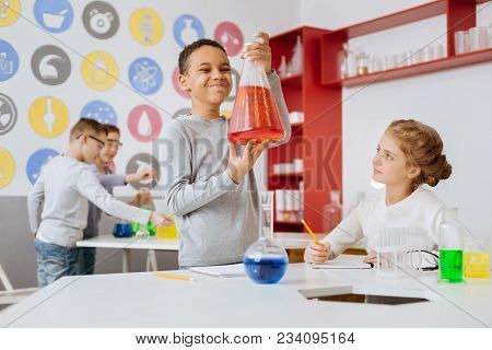 Content With Result. Upbeat Pre-teen Boy Holding A Big Flask With Red Chemical And Looking At It Wit