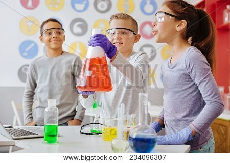 Check It Out. Upbeat Teenage Boy Lifting Up A Big Flask And Showing The Ongoing Reaction Inside It T