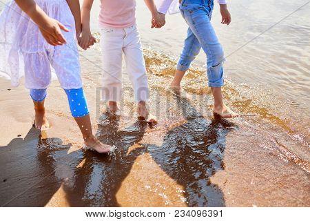 Barefoot girls walking down sandy beach along coastline in warm water on summer day