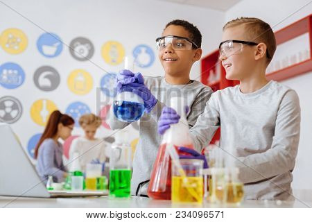 Surprising Reaction. Two Cheerful Teenage Male Students Looking At A Flask With A Blue Substance Pro