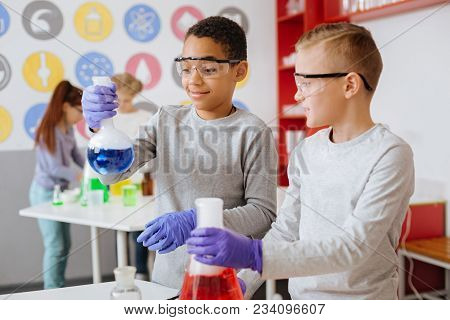 Fond Of Chemistry. Cheerful Teenage Boys Holding Chemical Flasks With Fuming Substances And Observin