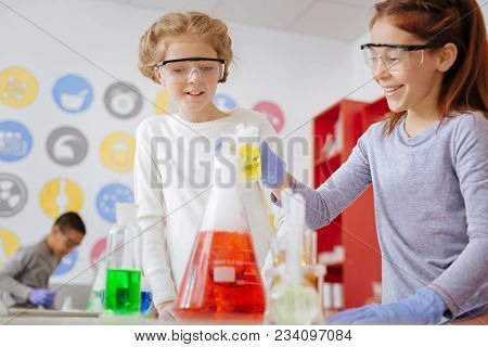 Chemistry Lovers. Upbeat Teenage Female Students Pouring Chemical Into The Flask And Smiling While C