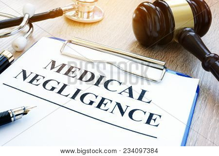 Clipboard With Documents About Medical Negligence On A Table.