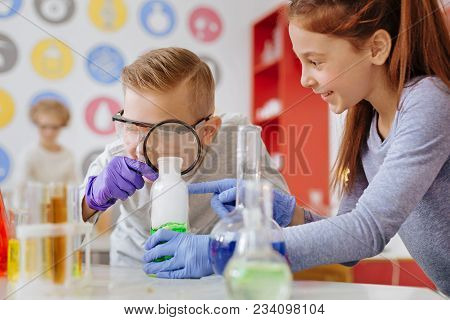 Examining Thoroughly. Joyful Teenage Boy Examining A Chemical Substance In The Flask With A Magnifyi