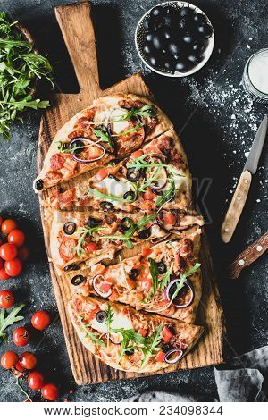 Flatbread Pizza Garnished With Fresh Arugula On Wooden Pizza Board, Top View, Vertical Composition