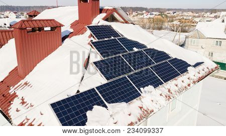 Solar Panels On The Roof Of The House After A Heavy Snowfall In The Winter. Renewable Energy Product