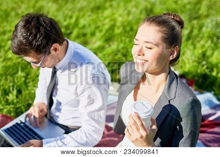 Young businesswoman with drink enjoying sunshine while her colleague networking near by