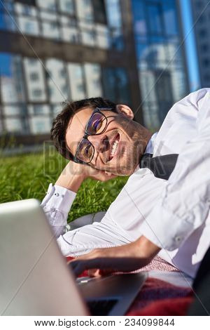 Young contemporary broker talking through video-chat in front of laptop on summer day outdoors