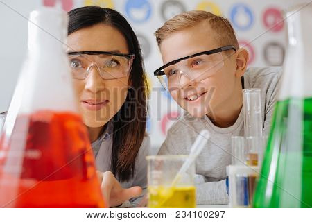 Favorite Science. The Close Up Of An Upbeat Teenage Student And His Young Chemistry Teacher Watching