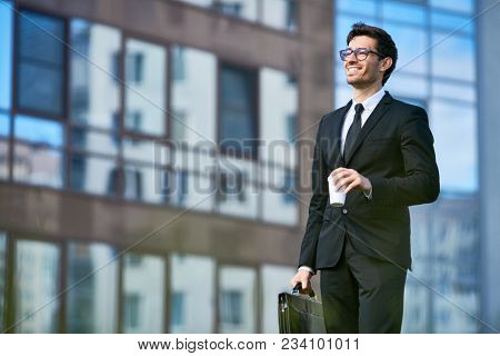 Cheerful banker in formalwear having coffee on his way to work in the morning