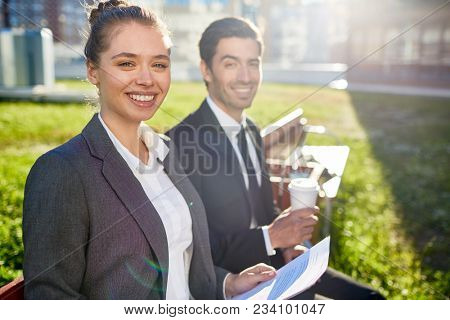 Cheerful businesswoman in formalwear looking at camera while having meeting with colleague in urban environment on sunny day