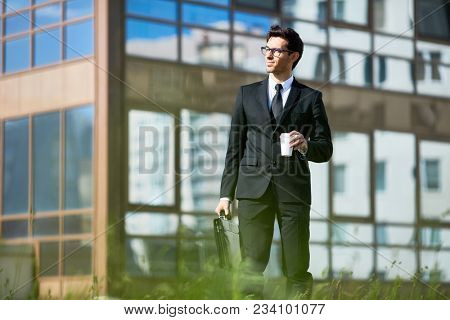 Young well-dressed man with drink and briefcase walking in urban environment and enjoying summer day